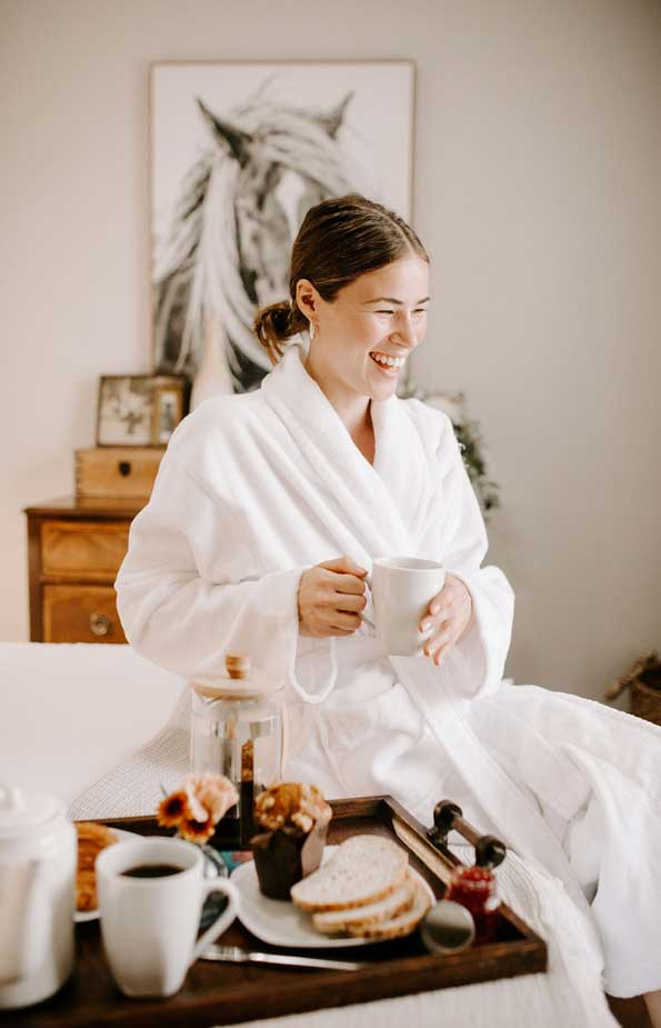 woman laughing on bed with coffee